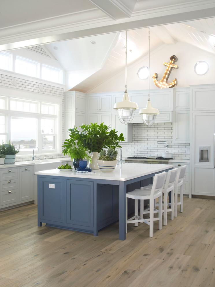 Inspiration for a large coastal l-shaped light wood floor kitchen remodel in San Diego with a farmhouse sink, shaker cabinets, blue cabinets, quartz countertops, white backsplash, paneled appliances, an island and subway tile backsplash