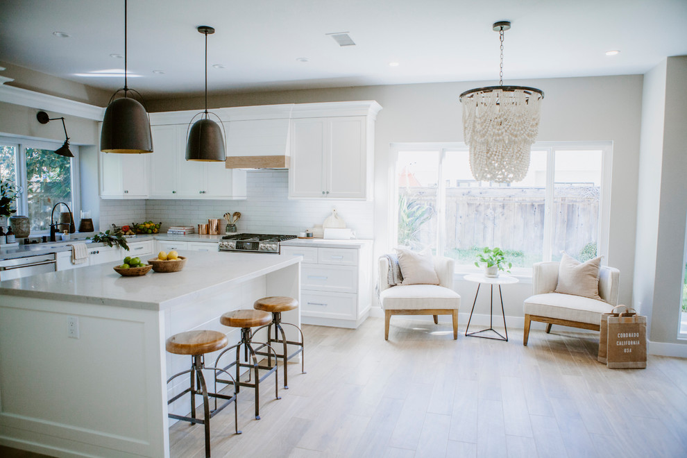 Open concept kitchen - mid-sized coastal l-shaped ceramic tile and brown floor open concept kitchen idea in San Diego with an undermount sink, shaker cabinets, white cabinets, quartz countertops, white backsplash, subway tile backsplash, stainless steel appliances and an island