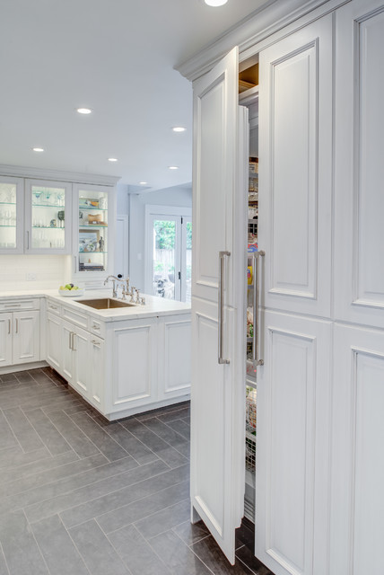 Example of a transitional u-shaped gray floor kitchen design in San Francisco with an undermount sink, raised-panel cabinets, white cabinets, quartz countertops, white backsplash, subway tile backsplash, paneled appliances and white countertops