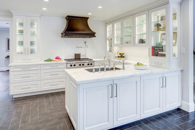 Transitional u-shaped gray floor kitchen photo in San Francisco with an undermount sink, raised-panel cabinets, white cabinets, white backsplash, subway tile backsplash, a peninsula, white countertops, quartz countertops and paneled appliances