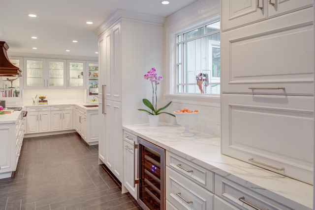 Inspiration for a transitional u-shaped gray floor kitchen remodel in San Francisco with an undermount sink, raised-panel cabinets, white cabinets, quartz countertops, white backsplash, subway tile backsplash, paneled appliances and white countertops