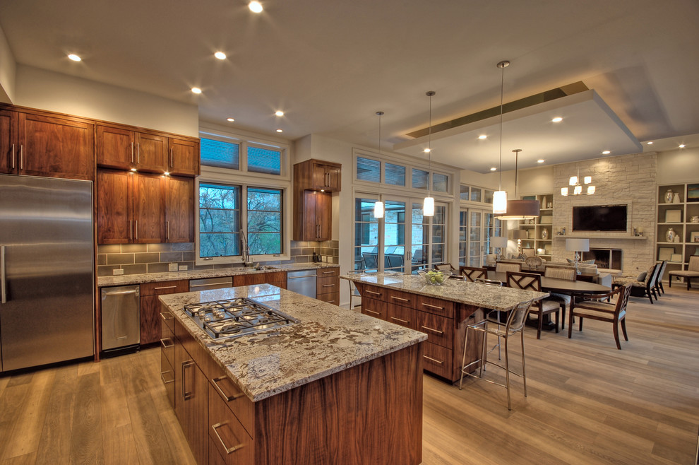 Open concept kitchen - transitional open concept kitchen idea in Austin with recessed-panel cabinets, dark wood cabinets and stainless steel appliances