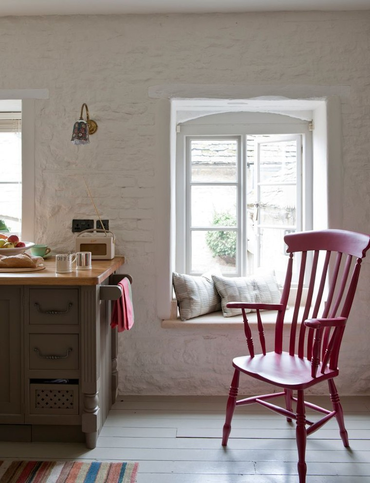 Eat-in kitchen - mid-sized farmhouse light wood floor eat-in kitchen idea in London with a farmhouse sink, flat-panel cabinets, medium tone wood cabinets, wood countertops, white backsplash, colored appliances and no island