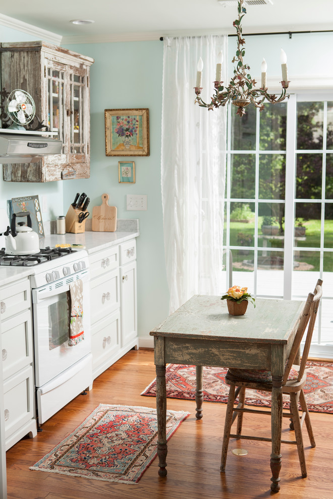 Inspiration for a shabby-chic style single-wall eat-in kitchen remodel in Wilmington with distressed cabinets, white appliances and shaker cabinets