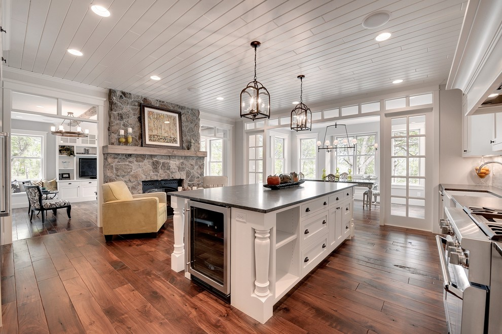 Large transitional l-shaped dark wood floor and brown floor enclosed kitchen photo in Minneapolis with a farmhouse sink, recessed-panel cabinets, white cabinets, stainless steel appliances, soapstone countertops and an island