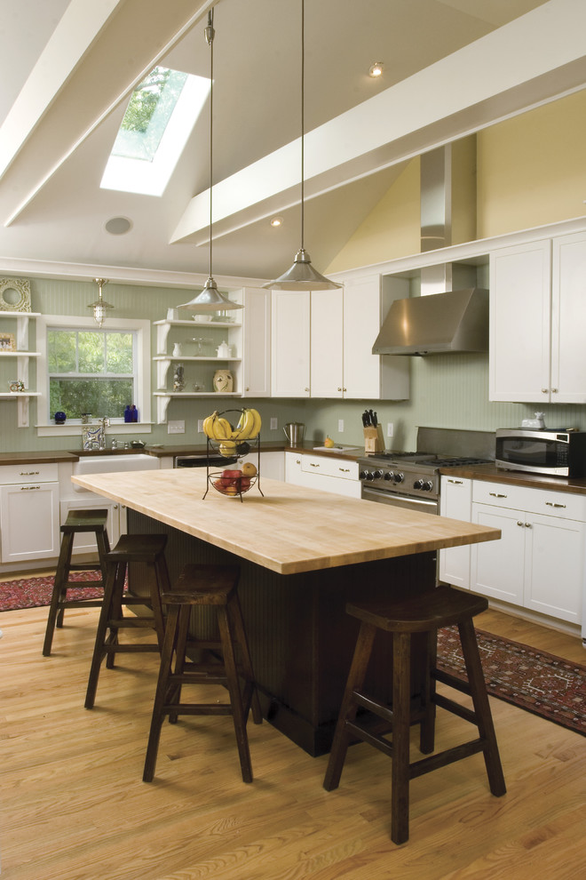Kitchen - transitional l-shaped kitchen idea in Other with wood countertops, a farmhouse sink, shaker cabinets, white cabinets and stainless steel appliances