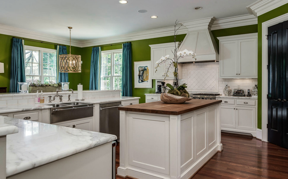 Elegant u-shaped dark wood floor kitchen photo in Charlotte with a farmhouse sink, recessed-panel cabinets, white cabinets, white backsplash, subway tile backsplash, stainless steel appliances and an island