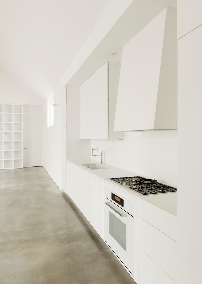 Example of a mid-sized trendy single-wall concrete floor open concept kitchen design in Houston with an undermount sink, flat-panel cabinets, white cabinets, white appliances, solid surface countertops, no island and white backsplash