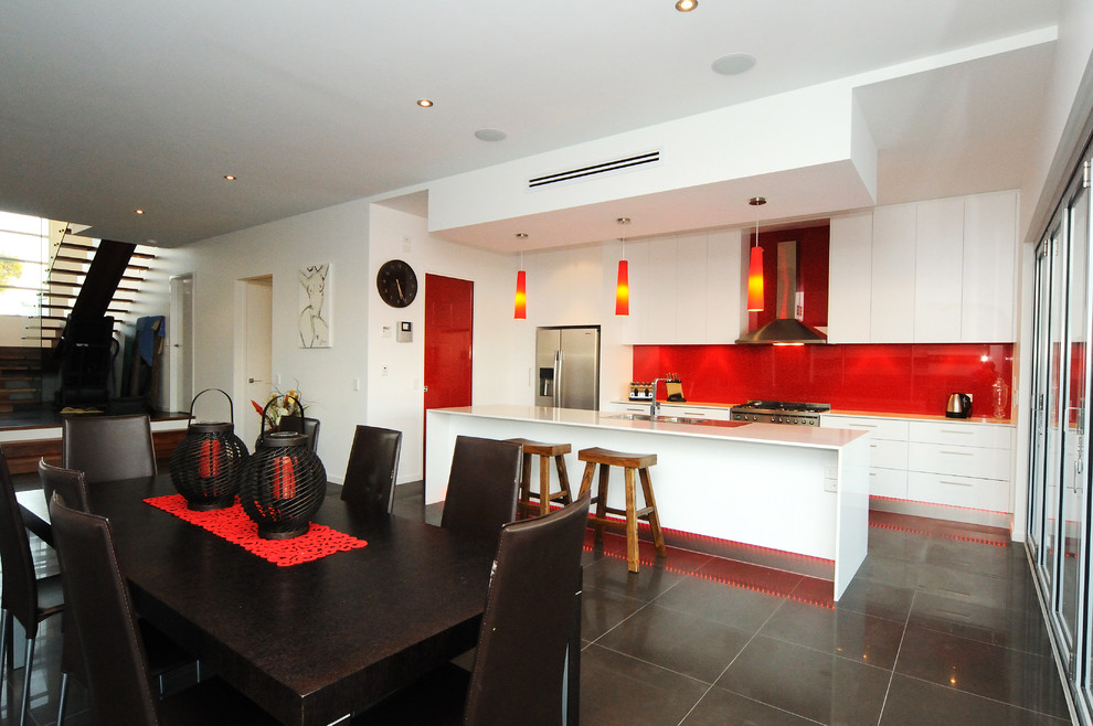 Inspiration for a contemporary galley open concept kitchen remodel in Brisbane with a double-bowl sink, flat-panel cabinets, white cabinets, red backsplash, glass sheet backsplash and stainless steel appliances