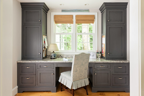 Dark gray built-in home office desk with a window view creates a stylish and chick nook.
