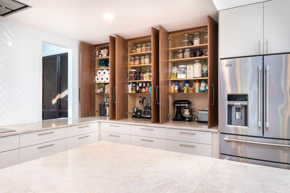 Kitchen pantry - large transitional l-shaped kitchen pantry idea in Portland with flat-panel cabinets, medium tone wood cabinets, quartzite countertops, white backsplash, ceramic backsplash, stainless steel appliances and an island