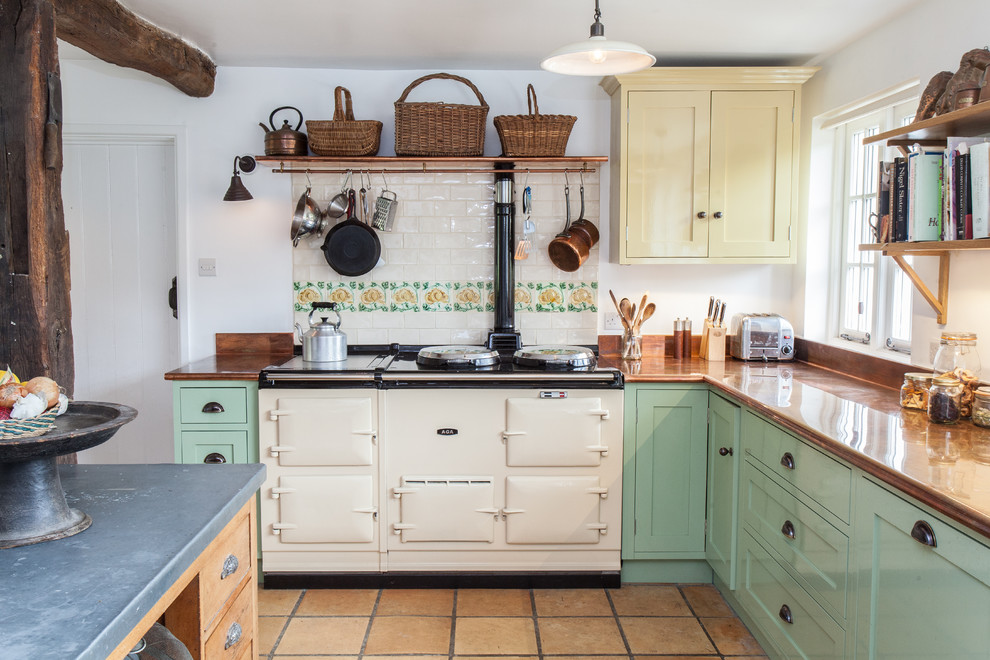 Example of a cottage l-shaped kitchen design in Hampshire with shaker cabinets, green cabinets, multicolored backsplash, subway tile backsplash, white appliances and an island