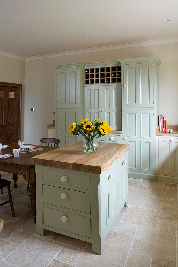 Example of a cottage kitchen design in Other with beaded inset cabinets and wood countertops