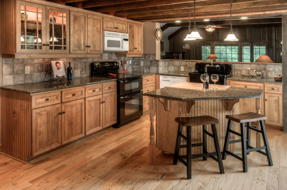 Example of a mountain style kitchen design in Omaha with a farmhouse sink, recessed-panel cabinets, medium tone wood cabinets, beige backsplash and black appliances