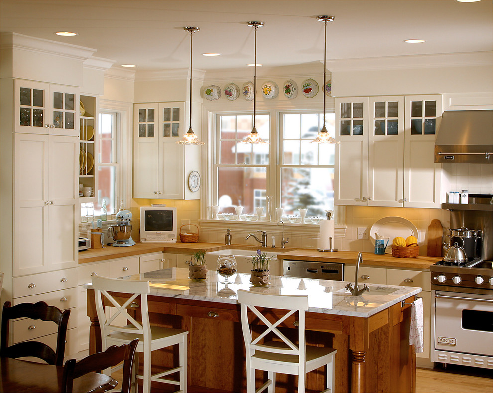 Elegant kitchen photo in Minneapolis with stainless steel appliances, a farmhouse sink and wood countertops
