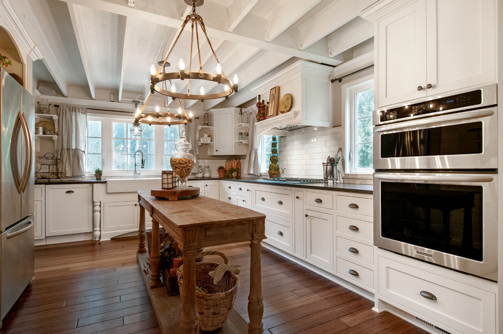Eat-in kitchen - cottage u-shaped medium tone wood floor and brown floor eat-in kitchen idea in Seattle with a farmhouse sink, shaker cabinets, white cabinets, white backsplash, subway tile backsplash, stainless steel appliances, quartz countertops and an island
