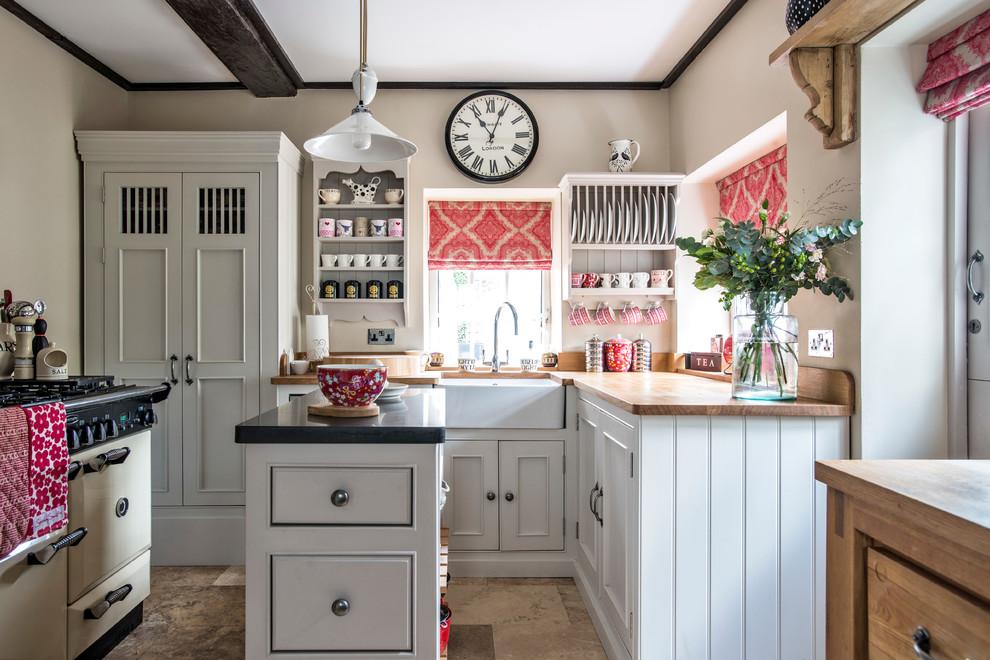 Foto de cocinas en L estrecha, de estilo de casa de campo, con fregadero sobremueble, armarios con rebordes decorativos, puertas de armario blancas, encimera de madera y una isla