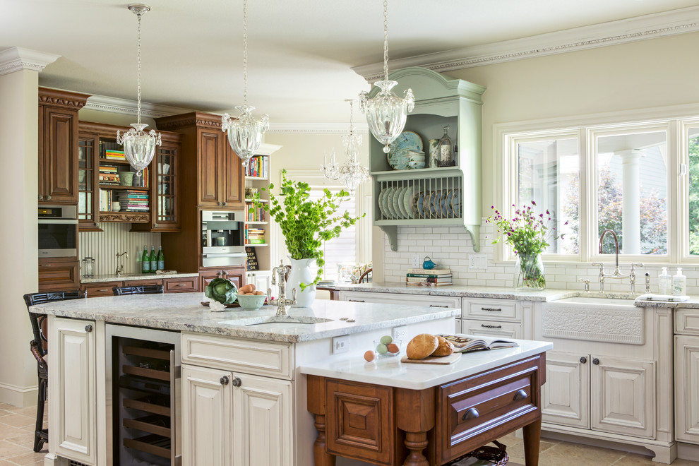 Kitchen - traditional l-shaped porcelain tile kitchen idea in Other with a farmhouse sink, raised-panel cabinets, white cabinets, granite countertops, white backsplash, subway tile backsplash, stainless steel appliances and an island