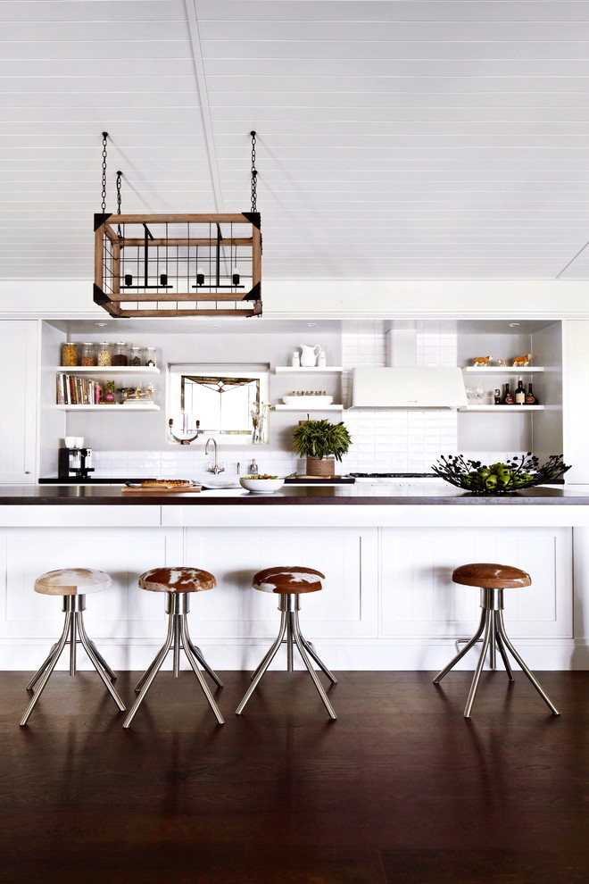 Inspiration for a large country galley dark wood floor open concept kitchen remodel in Melbourne with a farmhouse sink, shaker cabinets, white cabinets, wood countertops, white backsplash, ceramic backsplash, white appliances, an island and gray countertops