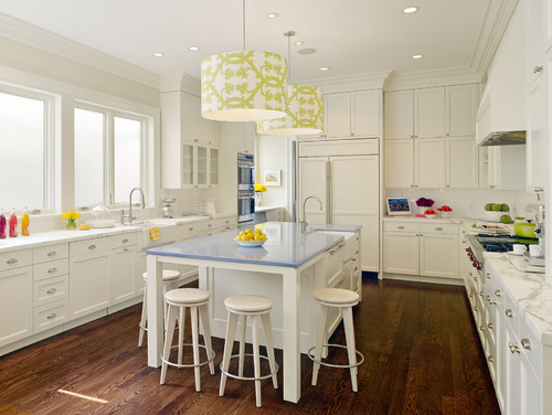 White kitchen with yellow-printed drum-shade ceiling lights and a blue island table surrounded by stools