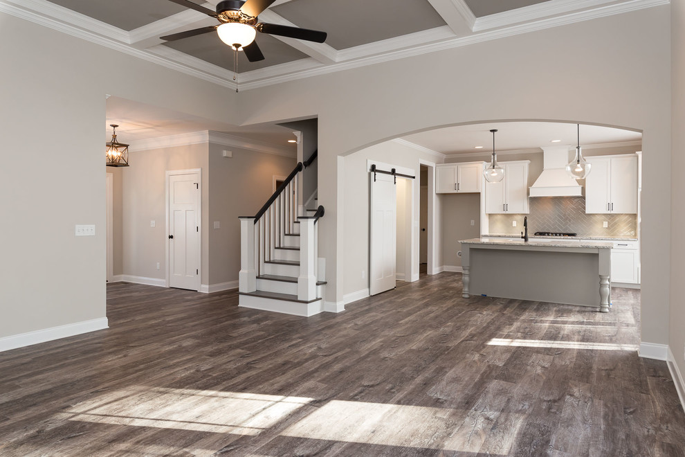 Open concept kitchen - mid-sized transitional single-wall vinyl floor and brown floor open concept kitchen idea in Raleigh with a farmhouse sink, shaker cabinets, white cabinets, granite countertops, gray backsplash, ceramic backsplash, stainless steel appliances and an island