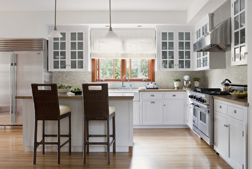 Example of a transitional l-shaped kitchen design in Los Angeles with stainless steel appliances, a farmhouse sink, glass-front cabinets, white cabinets, concrete countertops, beige backsplash and matchstick tile backsplash