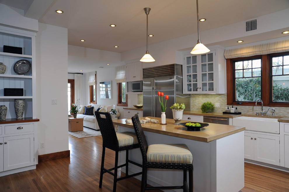 Example of a transitional kitchen design in Los Angeles with a farmhouse sink, glass-front cabinets, white cabinets, concrete countertops, beige backsplash, matchstick tile backsplash and stainless steel appliances