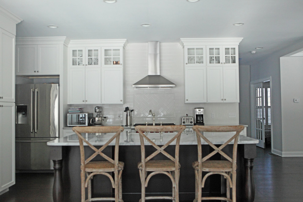 Example of a large arts and crafts u-shaped dark wood floor eat-in kitchen design in Providence with recessed-panel cabinets, white cabinets, granite countertops, white backsplash, subway tile backsplash, stainless steel appliances, an island and a farmhouse sink