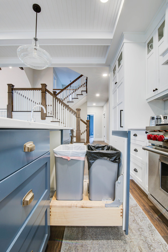 Example of a mid-sized arts and crafts single-wall medium tone wood floor and brown floor enclosed kitchen design in Calgary with a farmhouse sink, shaker cabinets, blue cabinets, quartz countertops, stainless steel appliances, an island and white countertops