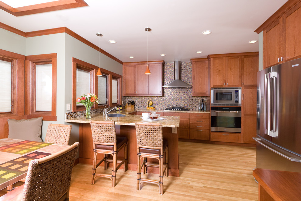 Example of a huge arts and crafts u-shaped light wood floor eat-in kitchen design in San Francisco with an undermount sink, shaker cabinets, medium tone wood cabinets, granite countertops, multicolored backsplash, glass tile backsplash, stainless steel appliances and a peninsula