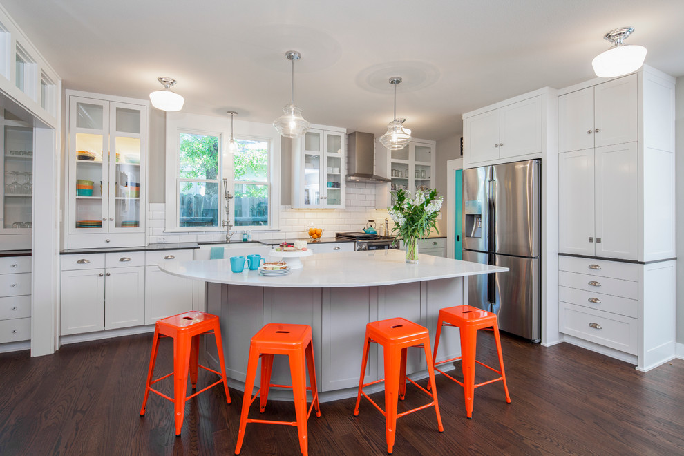 Example of a mid-sized transitional l-shaped dark wood floor kitchen design in Austin with a farmhouse sink, recessed-panel cabinets, white cabinets, quartz countertops, white backsplash, stainless steel appliances, an island and subway tile backsplash