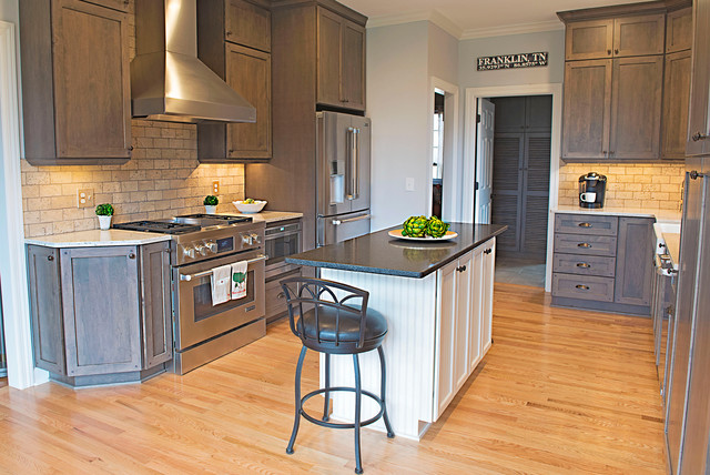 Eat-in kitchen - large craftsman l-shaped medium tone wood floor eat-in kitchen idea in Nashville with a farmhouse sink, shaker cabinets, distressed cabinets, laminate countertops, beige backsplash, stone tile backsplash, stainless steel appliances and an island