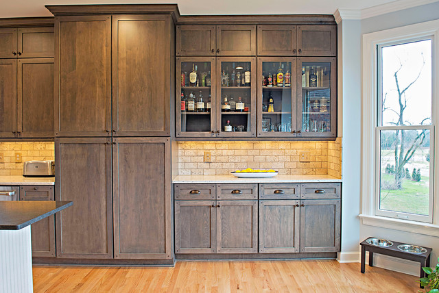 Example of a large arts and crafts l-shaped medium tone wood floor eat-in kitchen design in Nashville with shaker cabinets, an island, a farmhouse sink, distressed cabinets, laminate countertops, beige backsplash, stone tile backsplash and stainless steel appliances