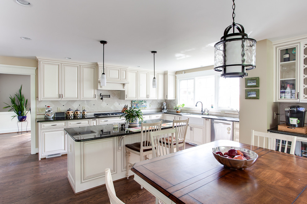 Eat-in kitchen - large traditional eat-in kitchen idea in DC Metro with a farmhouse sink, raised-panel cabinets, white backsplash, stainless steel appliances and granite countertops
