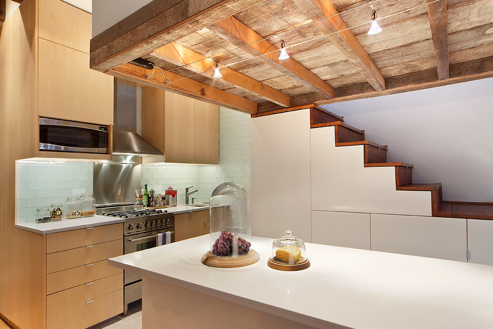 Eat-in kitchen - mid-sized industrial l-shaped ceramic tile eat-in kitchen idea in New York with an undermount sink, flat-panel cabinets, medium tone wood cabinets, granite countertops, glass tile backsplash, stainless steel appliances and an island
