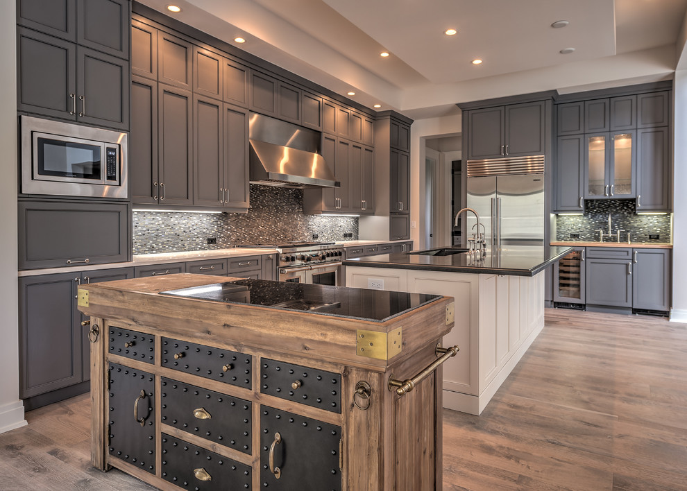 Inspiration for a huge transitional medium tone wood floor kitchen remodel in Miami with an undermount sink, recessed-panel cabinets, gray cabinets, gray backsplash, mosaic tile backsplash, stainless steel appliances and two islands