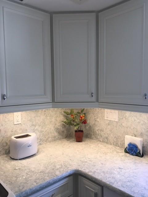 Kitchen - mid-sized coastal kitchen idea in Miami with recessed-panel cabinets, white cabinets, quartz countertops, stone slab backsplash and white appliances