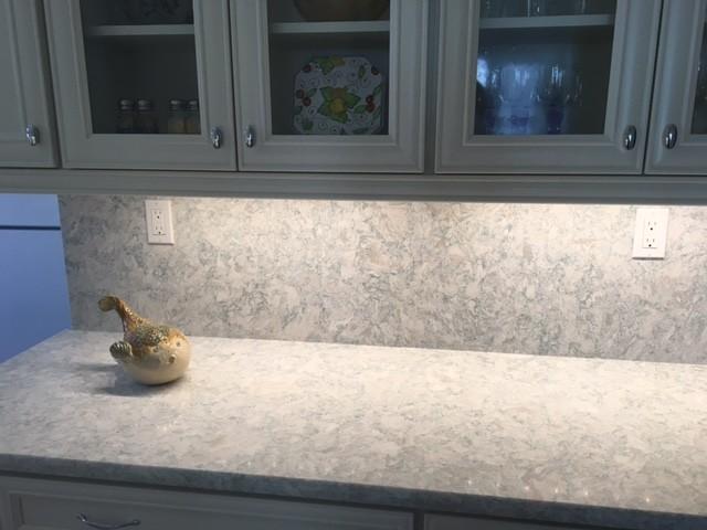 Kitchen - mid-sized coastal kitchen idea in Miami with white cabinets, quartz countertops, recessed-panel cabinets, stone slab backsplash and white appliances