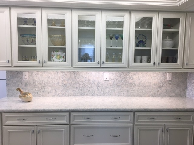 Example of a mid-sized beach style kitchen design in Miami with white cabinets, quartz countertops, stone slab backsplash, white appliances and recessed-panel cabinets