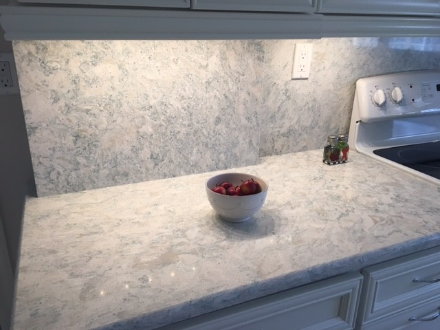 Inspiration for a mid-sized coastal kitchen remodel in Miami with recessed-panel cabinets, white cabinets, quartz countertops, stone slab backsplash and white appliances
