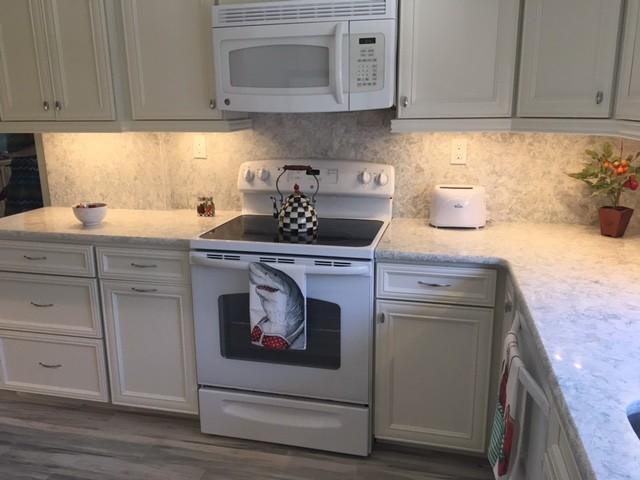 Example of a mid-sized beach style kitchen design in Miami with recessed-panel cabinets, white cabinets, quartz countertops, stone slab backsplash and white appliances