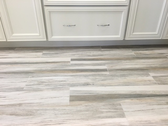 Inspiration for a mid-sized coastal kitchen remodel in Miami with recessed-panel cabinets, white cabinets, white appliances, quartz countertops and stone slab backsplash