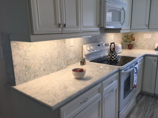 Mid-sized beach style kitchen photo in Miami with white cabinets, quartz countertops, stone slab backsplash, white appliances and recessed-panel cabinets