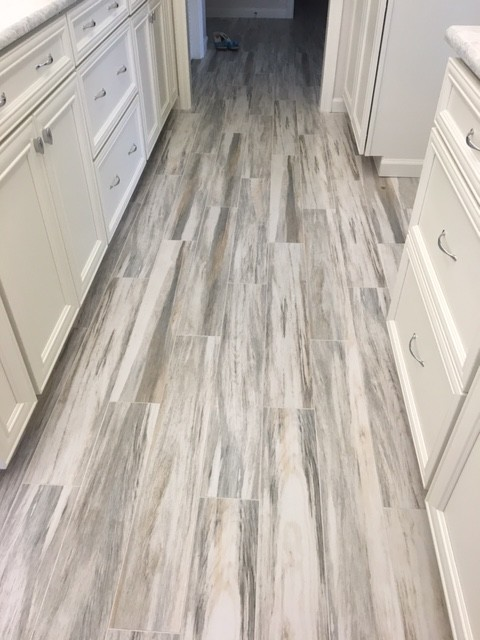 Inspiration for a mid-sized coastal porcelain tile kitchen remodel in Miami with recessed-panel cabinets, white cabinets, white appliances, an undermount sink, quartz countertops and stone slab backsplash
