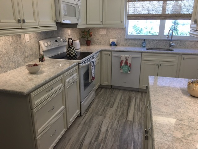 Kitchen - mid-sized coastal porcelain tile kitchen idea in Miami with recessed-panel cabinets, white cabinets, stone slab backsplash, white appliances, an undermount sink and quartz countertops