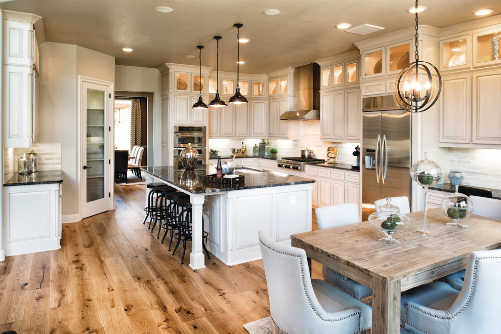 Elegant l-shaped medium tone wood floor eat-in kitchen photo in Philadelphia with an undermount sink, raised-panel cabinets, white cabinets, white backsplash, stainless steel appliances and an island
