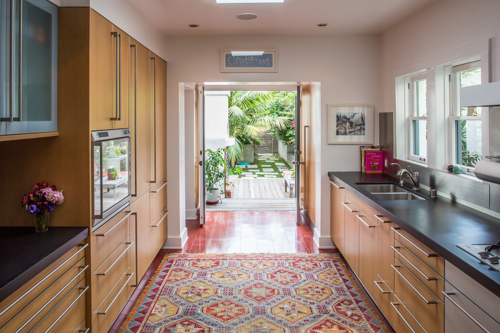 Example of a mid-sized trendy galley porcelain tile enclosed kitchen design in Los Angeles with an undermount sink, flat-panel cabinets, medium tone wood cabinets, metallic backsplash, solid surface countertops, stone tile backsplash, stainless steel appliances and no island