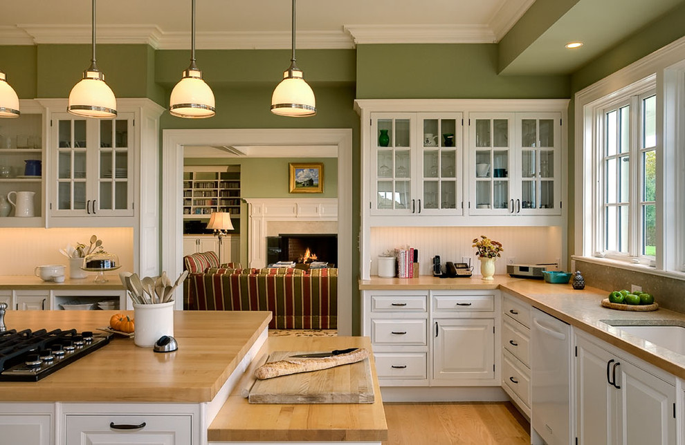 Inspiration for a timeless enclosed kitchen remodel in New York with glass-front cabinets, wood countertops, white cabinets, an undermount sink, white backsplash and white appliances
