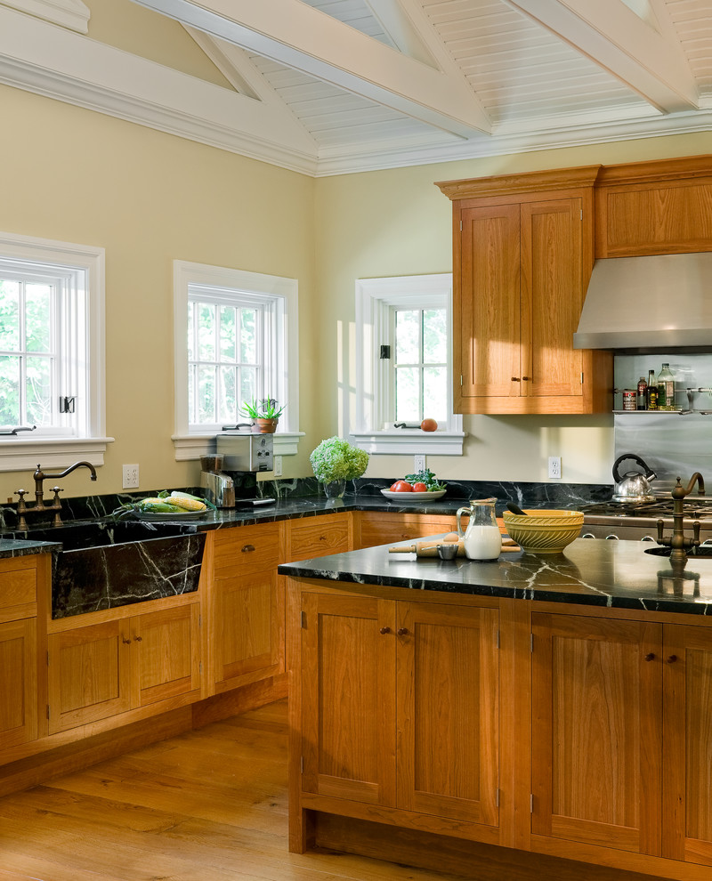Example of a farmhouse eat-in kitchen design in New York with an integrated sink, shaker cabinets, medium tone wood cabinets and soapstone countertops