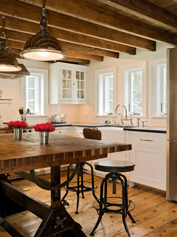 Eat-in kitchen - cottage eat-in kitchen idea in New York with a farmhouse sink, recessed-panel cabinets, white cabinets, white backsplash, subway tile backsplash, soapstone countertops and stainless steel appliances